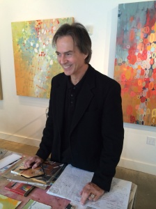 Langford in the studio showing his paintings